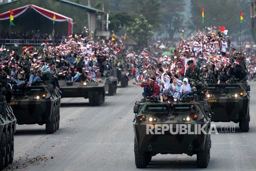 Peringatan HUT TNI ke-72. Warga menunmpang kendaraa tempur saat defile alutsista TNI pada Upacara Peringatan HUT TNI ke-72 di Dermaga Indah Kiat, Cilegon, Banten, Kamis (5/10)