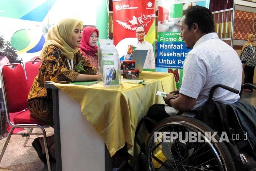 Pertugas BPJS Ketenagakerjaan berbincang dengan seorang penyandang disabilitas pada acara Gebyar Pemberian Manfaat Kepada Penyandang Disabilitas Se Provinsi Jawa Barat oleh BPJS Ketenagakerjaan, di Aula Pusdai, Kota Bandung, Selasa (8/8).