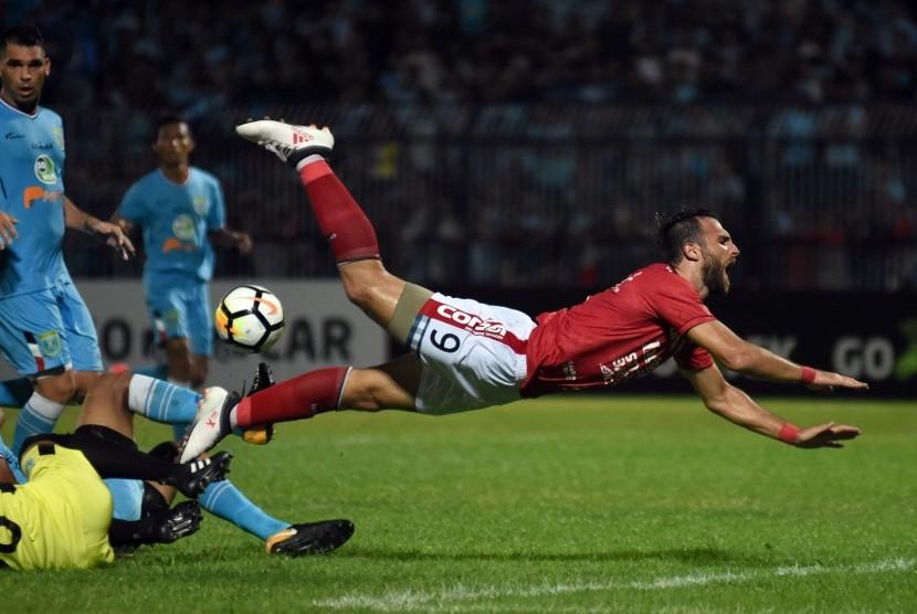 Pesepak bola Bali United Ilija Spasojevic terjatuh saat bertabrakan dengan pesepak bola Persela Lamongan dalam laga Liga 1 di Stadion Surajaya, Lamongan, Jawa Timur, Senin (16/4). Persela Lamongan ditahan imbang Bali United dengan skor 1-1.
