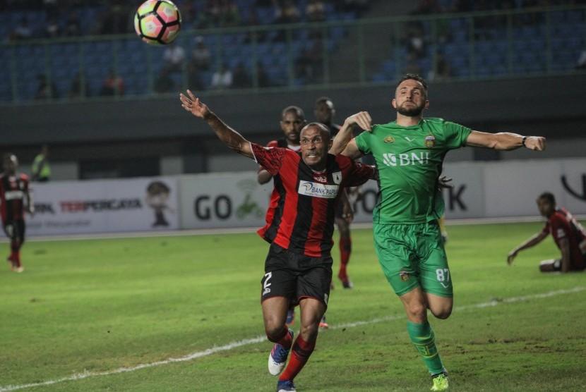 Pesepak bola Bhayangkara FC Ilija Spasojevic (kanan) berebut bola dengan pesepak bola Persipura Jayapura Rony Esar Beroperay (kiri), pada pertandingan Gojek Traveloka Liga 1 di Stadion Patriot Candrabaga, Bekasi, Jawa Barat, Sabtu (9/9).