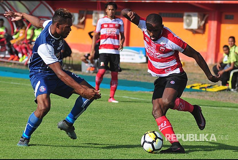 Pesepak bola Madura United (MU) Greg Nwokolo (kanan) berusaha melewati pesepak bola Arema FC, Israel Wamiau dalam kompetisi Go-Jek  Liga 1 di Stadion Gelora Ratu Pamelingan (SGRP) Pamekasan, Jawa Timur,  Sabtu (21/4).