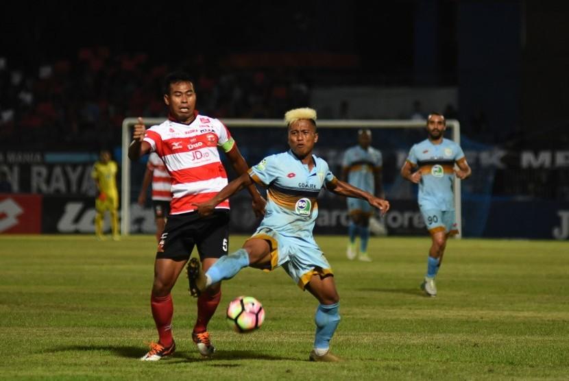 Pesepak bola Persela Lamongan Moch. Fahmi Al-Ayyubi (kanan) berebut bola dengan pesepak bola Madura United FC Munhar (kiri) dalam pertandingan Gojek Traveloka Liga 1 di Stadion Surajaya Lamongan, Jawa Timur, Jumat (21/4).
