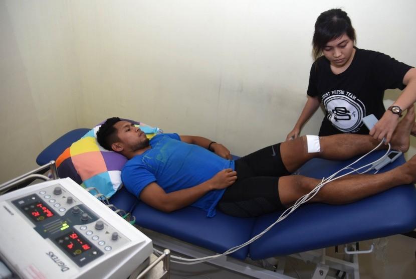 Pesepak bola tim nasional Indonesia Andik Vermansyah (kiri) menjalani terapi penyembuhan cedera di Physiopreneur Sport Physiotherapy kawasan Surabaya Barat, Jawa Timur, Senin (16/1).