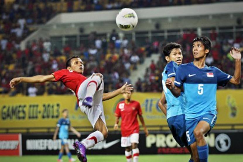 Pesepakbola Indonesia Hendra Adi Bayauw (kiri) berebut bola dengan pesepakbola Singapura Ali Hudzaifi (kanan) dalam pertandingan babak kualifikasi grup E Piala Asia (AFC) U-22 di Stadion Utama Riau, Pekanbaru, Riau, Ahad (15/7)