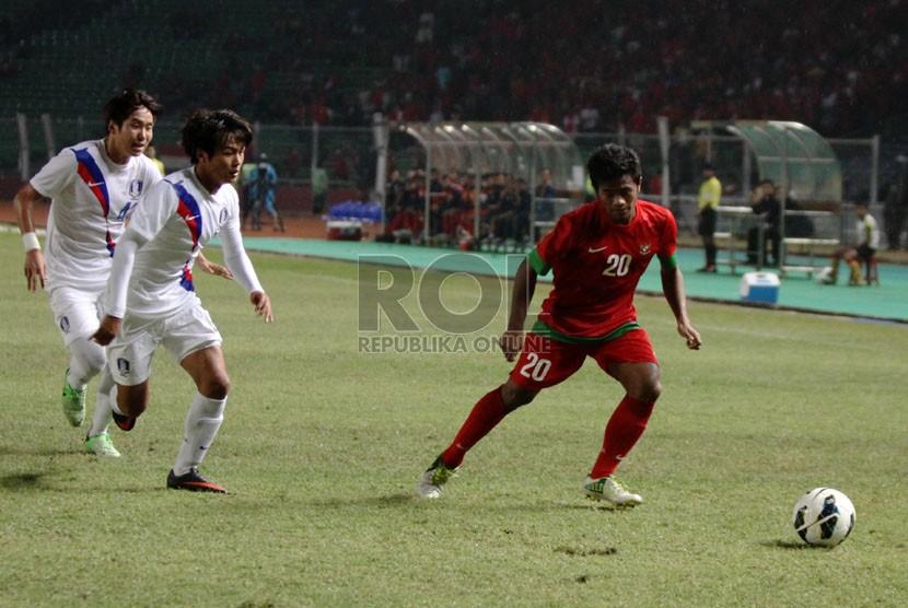 Pesepakbola Indonesia Ilham Udin (kanan) berhadapan dengan pemain Korea Selatan dalam laga kualifikasi group G AFC U-19 di Gelora Bung Karno, Senayan, Jakarta, Sabtu (12/10).   (Republika/Yasin Habibi)