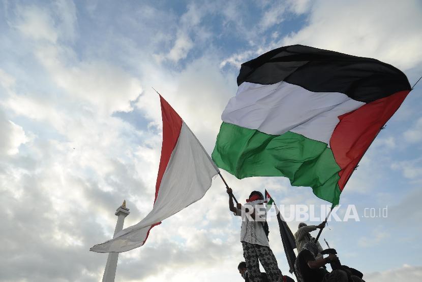Peserta aksi solidaritas Palestina mengibarkan bendera Palestina dan Indonesia dalam aksi solidaritas Palestina di Monumen Nasional, Jakarta, Ahad (17/12).
