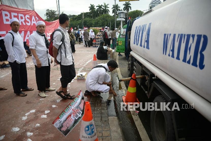 Peserta Aksi super damai 212 mengambil air wudhu sebelum melaksanakan sholat Jumat di Kawasan Silang Monas, Jakarta, Jumat,(2/12)