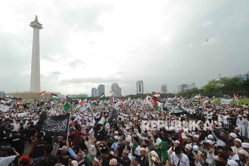 Peserta perempuan aksi solidaritas Palestina mengibarkan bendera dalam aksi solidaritas Palestina di Monumen Nasional, Jakarta, Ahad (17/12).