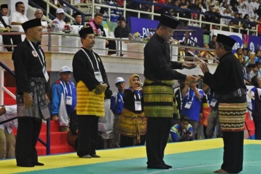 Pesilat Senior Tri Sipit S (kanan) menyerahkan senjata golok kepada Wakil Ketua PB IPSI Edhy Prabowo (kedua kanan) saat seremoni