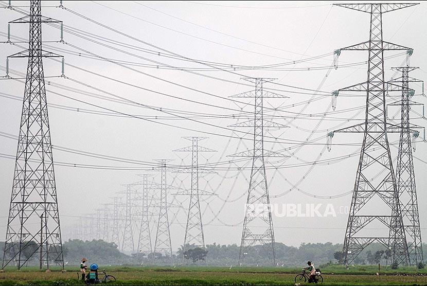 Petani beraktivitas di sawah dengan latar belakang tower sutet di kawasan Tawang Sari, Sukoharjo, Jawa Tengah, Jumat (1/12). PT PLN Persero mencatat daya mampu pasokan jaringan listrik Jawa-Bali hingga November mencapai 30.000 megawatt (MW), terdapat cadangan listrik mencapai 7.000-8.000 MW atau sebesar 31 persen.
