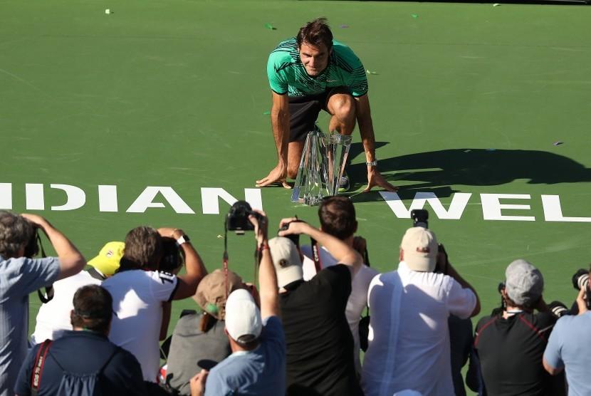 Petenis asal Swiss, Roger Federer berpose bersama trofi Indian Wells Terbuka 2017, Ahad (19/3). Federer mengalahkan Stanislas Wawrinka di partai final.