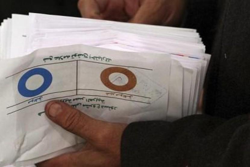 Petugas anggota panitia Referendum Mesir menghitung lembar suara dengan suara tidak