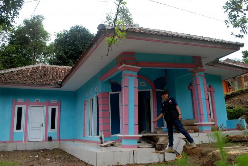 Petugas Badan Penanggulangan Bencana Daerah (BPBD) menunjukkah retakan di salah satu rumah yang rusak berat akibat bencana pergerakan tanah di Desa Nagrak Jaya, Kecamatan Curug Kembar, Sukabumi, Jawa Barat, Kamis (18/8).