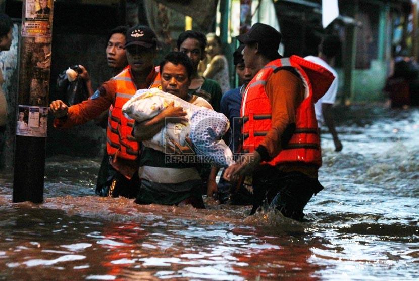 Petugas Basarnas mengevakuasi korban banjir di kawasan Kampung Pulo, Jakarta, Ahad (12/1).  (Republika/Yasin Habibi)