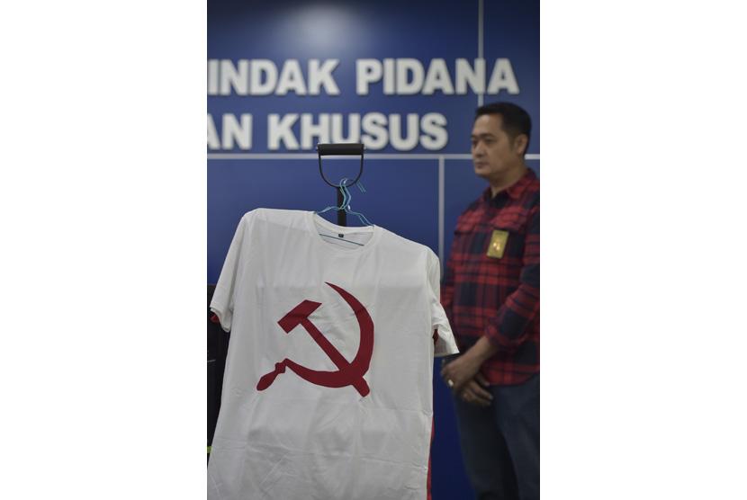 Petugas berdiri di dekat barang bukti berupa kaus berlambang palu arit saat rilis penangkapan tersangka penjual kaus berlogo palu arit melalu media daring di Bareskrim Polri, Jakarta, Jumat (30/12).