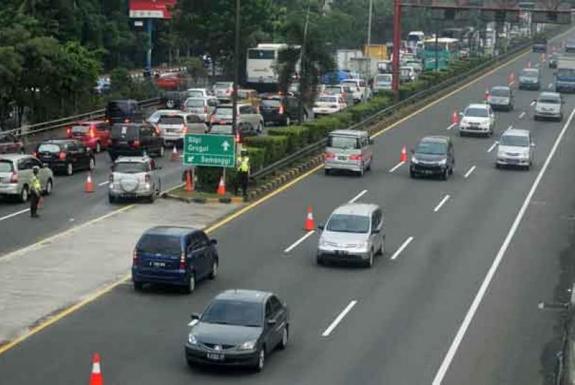 Petugas dari Kepolisian membantu mengatur arus lalu lintas di tol dalam kota di Kawasan Semanggi saat uji coba contra flow atau sistim melawan arus lalu lintas di Jakarta, Selasa (1/5).