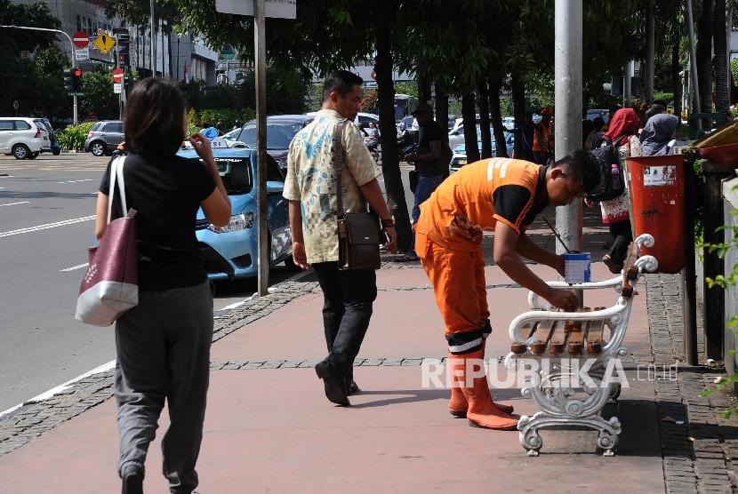 Petugas Dinas Kebersihan DKI mengecat bangku di sepanjang jalur pedestrian Jalan MH Thamrin, Jakarta Pusat, Jumat (4/3). (Republika/Tahta Aidilla)