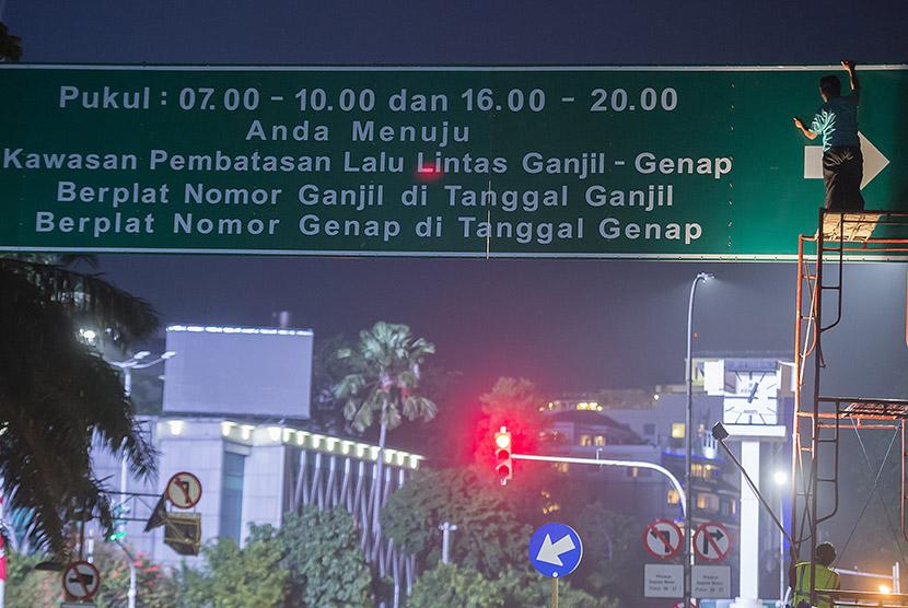 Petugas Dinas Perhubungan menyelesaikan pekerjaan pemasangan papan informasi penerapan sistem ganjil dan genap di Jalan Kebon Sirih, Jakarta, Sabtu (27/8).