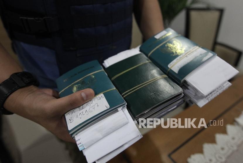 Petugas Imigrasi Bandara Soekarno-Hatta menujukkan sejumlah Passport calon Tenaga Kerja Indonesia (TKI) yang diduga ilegal di Kantor imigrasi Soekarno-Hatta Tangerang, Banten, Ahad (9/10).