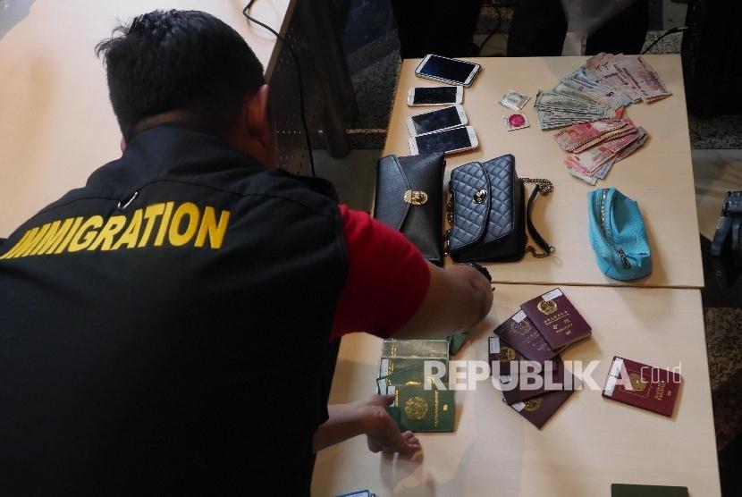 Petugas imigrasi meperlihatkan barang bukti razia keimigrasian saat rilis operasi pengawasan orang asing/ilustrasi.