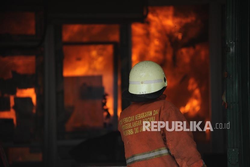 Petugas kebakaran berada di sejumlah pertokoan yang terbakar di jalan Sabang, Jakarta, Ahad (08/10).