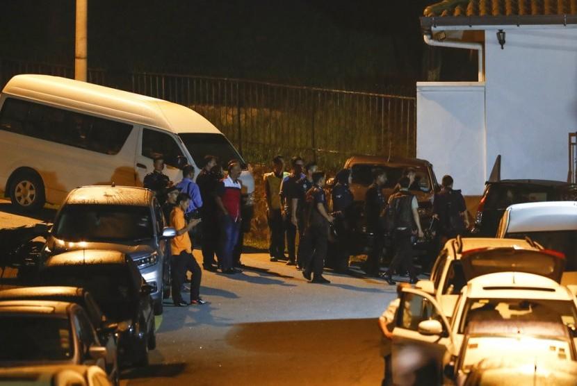 Petugas kepolisian berkumpul di luar kediaman mantan PM Malaysia Najib Razak, Kamis (17/5). Polisi menggeledah rumah Najib selama enam jam mencari bukti pencucian uang.