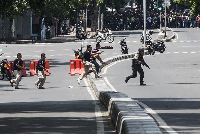 Petugas kepolisian berlari menuju ke arah gedung Sarinah untuk melakukan pengejaran terhadap pelaku  penyerangan yang dilakukan sejumlah teroris ke beberapa gedung dan pos polisi di  Jakarta, Kamis (14/1).
