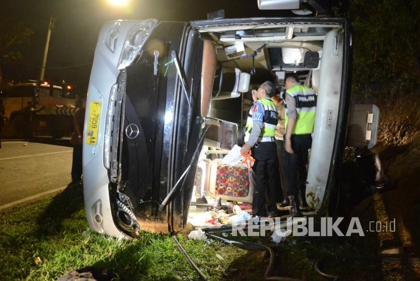 Petugas kepolisian memeriksa bis saat evakuasi kecelakaan bus pariwisata di tanjakan Emen, Kabupaten Subang, Sabtu (10/2).