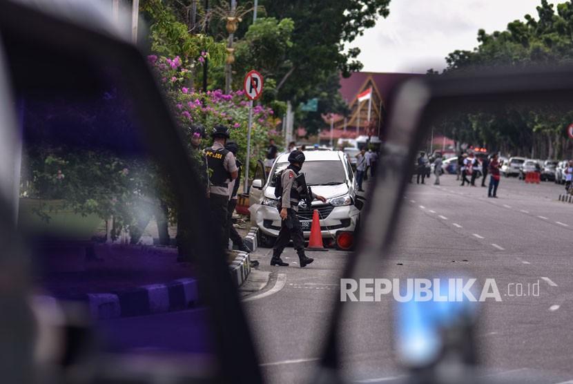 Petugas kepolisian memeriksa mobil minibus yang digunakan pelaku teror untuk menyerang Polda Riau, di Pekanbaru, Riau, Rabu (16/5).