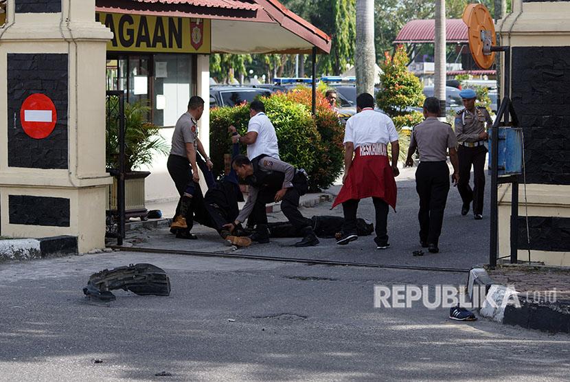 Petugas kepolisian mengevakuasi dua jenazah pelaku penyerangan di jalan pintu masuk Polda Riau di Pekanbaru, Riau, Rabu (16/5).