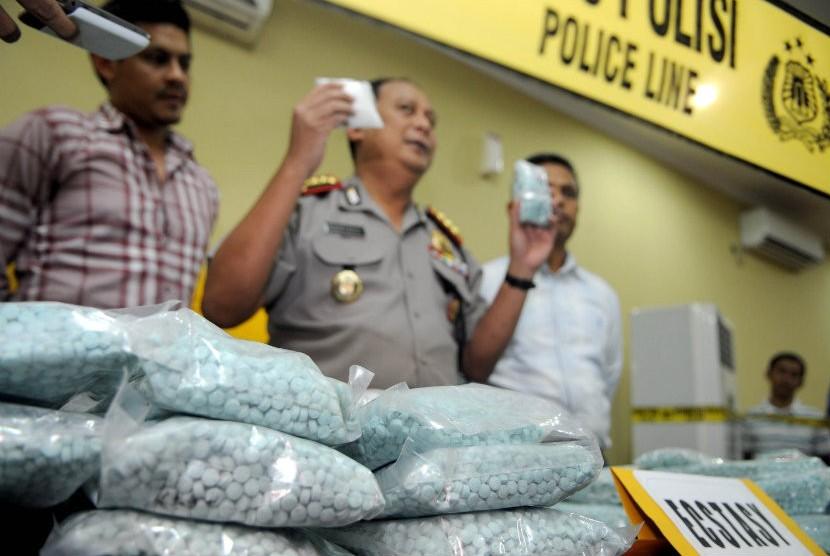 Petugas kepolisian menunjukan tiga orang tersangka beserta barang bukti berupa narkoba jenis shabu dan ecstasy saat jumpa pers di Polres Jakarta Barat, Selasa (19/6). (Prayogi/Republika)