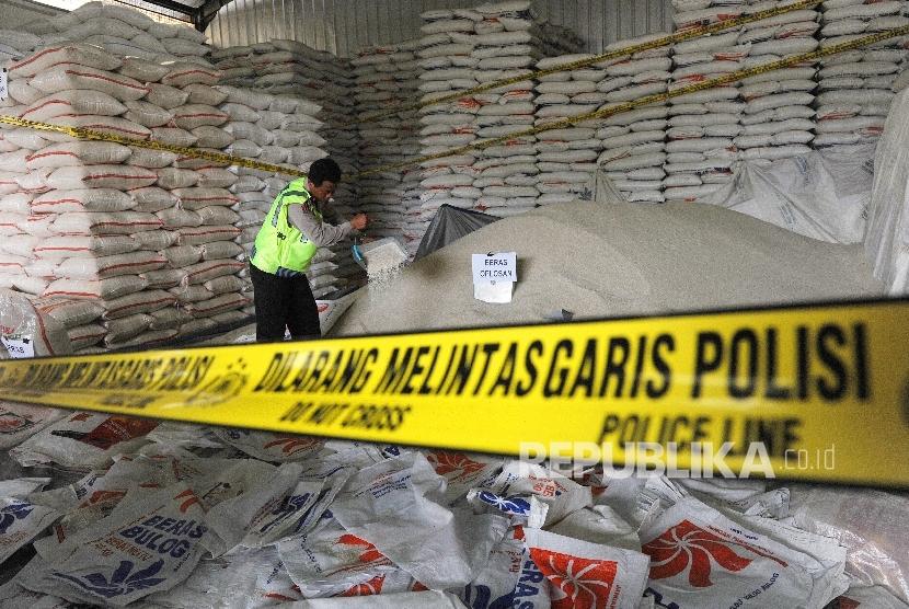 Petugas kepolisian menunjukkan barang bukti beras oplosan di salah satu gudang di Pasar Induk Beras Cipinang, Jakarta, Jumat (7/10).