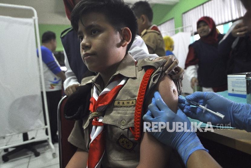 Petugas kesehatan memberikan suntikan imunisasi Measleas Rubela (MR) kepada sejumlah siswa-siswi saat acara Kampanye Measles Rubella (MR) dan Campak sekaligus Peringati Asean Dengeu Day 2017 di SMPN 103 Cijantung, Jakarta, Rabu (2/7).
