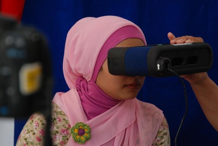 Petugas melakukan perekaman iris mata warga saat pembuatan KTP elektronik (E-KTP) di RW010 Desa Rawapanjang, Bojonggede,Bogor.Ahad (22/7).