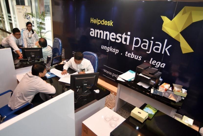 Petugas melayani wajib pajak untuk memperoleh informasi mengenai kebijakan amnesti pajak (tax amnesty) di Help Desk Kantor Wilayah Direktorat Jenderal Pajak I, Jakarta Selatan, Senin (19/9).
