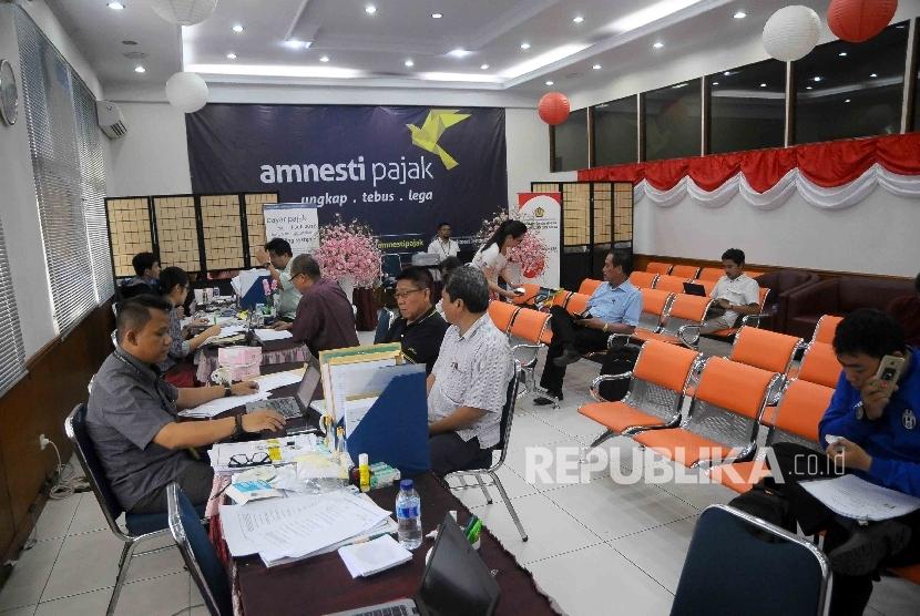 Petugas melayani wajib pajak yang mengikuti program pengampunan pajak (tax amnesty) di Kantor Pelayanan Pajak Tabah Abang, Jakarta Pusat, Kamis (29/12).