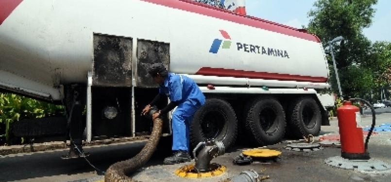 Petugas memasang alat pengisian bahan bakar minyak (BBM) premium dari tanki di SPBU Abdul Muis, Jakarta.