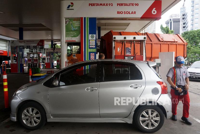 Petugas membantu konsumen mengisi Bahan Bakar Minyak (BBM) pada kendaraan di SPBU Abdul Muis, Jakarta, Ahad (17/12).