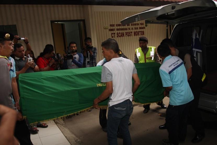 Petugas membawa jenazah anggota polisi Polsek Senen Bripka Taufik Hidayat setibanya di RS Polri Kramat Jati, Jakarta, Selasa (19/1).