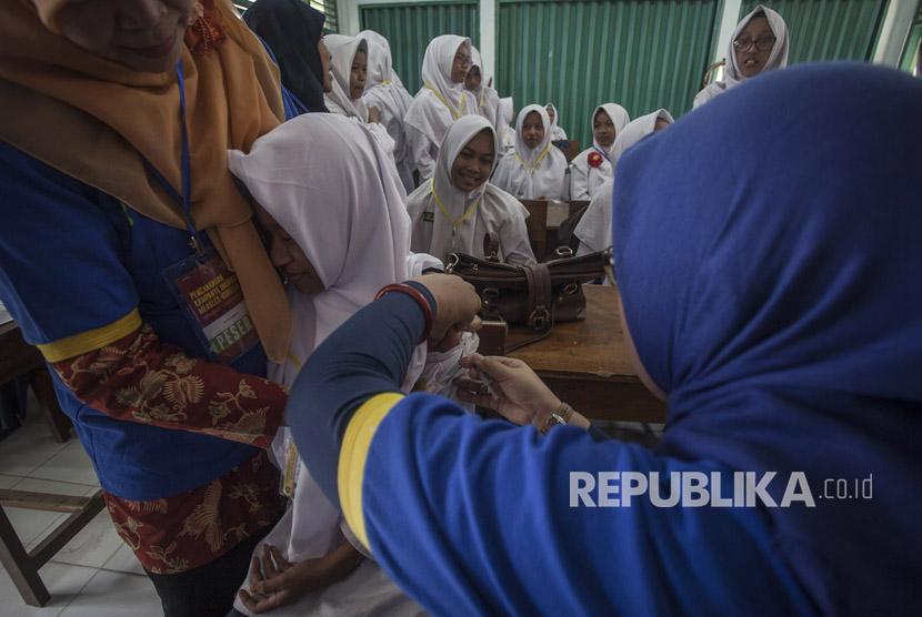 Petugas memberikan vaksin Measless Rubella (MR) kepada pelajar saat acara Pencanangan Kampanye Imunisasi MR di Madrasah Tsanawiah 10, Sleman, DI Yogyakarta, Senin (1/8).