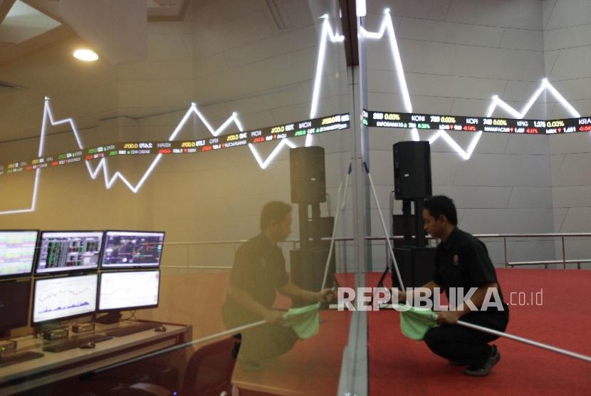 Petugas berdiri di dekat papan elektronik yang menunjukkan pergerakan indeks harga saham gabungan (IHSG) di gedung Bursa Efek Indonesia.