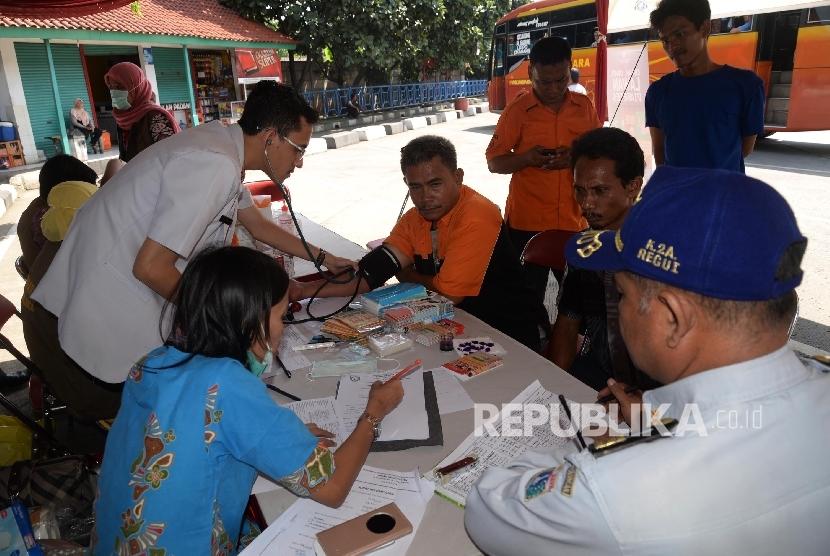 Petugas memeriksa kesehatan sopir angkutan Lebaran di posko kesehatan Terminal Kampung Rambutan, Jakarta, Jumat (24/6). (Republika/ Yasin Habibi)