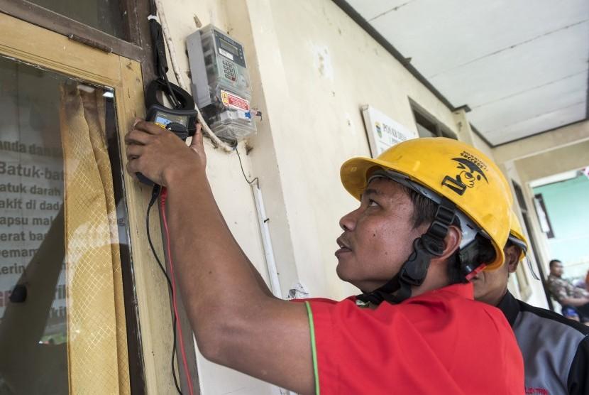 Petugas memeriksa tegangan listrik saat peresmian jaringan listrik pedesaan di Kampung Sukasenang, Desa Tanjung Karang, Kabupaten Tasikmalaya, Jawa Barat, Kamis (2/11).