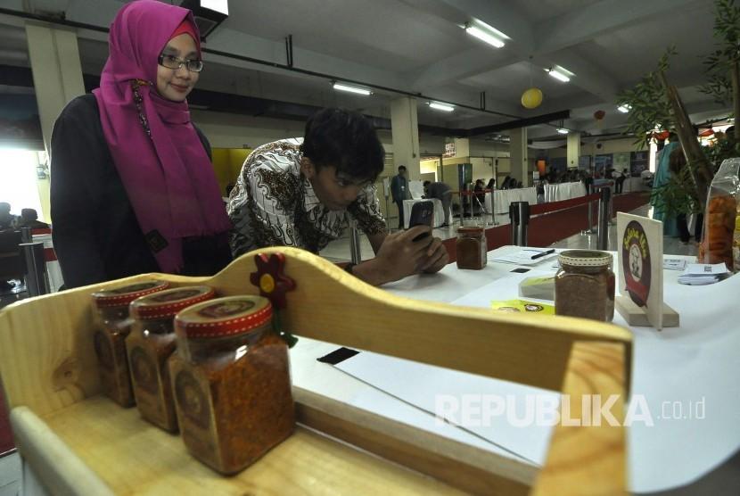 Petugas memotret foto salah satu produk UMKM yang telah didaftrakan untuk didaringkan, dengan berpartisipasi dalam program gerakan meng-online-kan 100.000 UMKM di Pasar Ciroyom, Kota Bandung, Jumat (31/3)