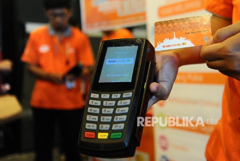 Petugas memperlihatkan penggunaan e-Money Witami Syariah dengan memakai alat EDC usai penyerahan sertifikat e-Money Syariah di Jakarta, Senin (28/3). (Republika/Tahta Aidilla)