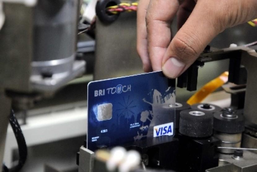 Petugas menarik sebuah kartu kredit pada proses pembuatan kartu kredit di 'embossing room' kartu kredit BRI di Jakarta.