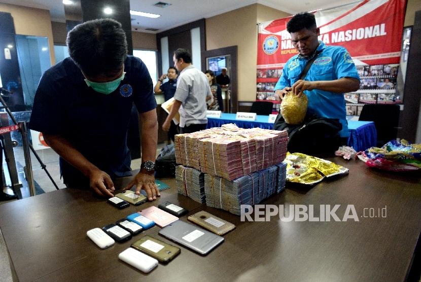 Petugas menata barang bukti uang tunai dan sabu sebelum rilis pengungkapan penyelundupan narkotia di perbatasan di BNN, Jakarta, Selasa (12/9).