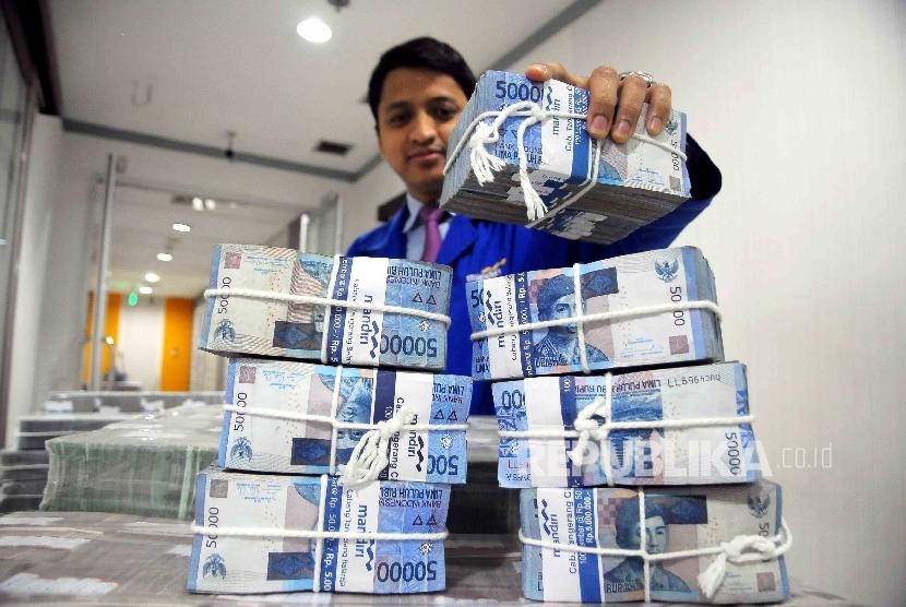 Petugas mendata uang Rupiah di ruang penyimpanan uang Bank Mandiri, Jakarta, Selasa (15/11).