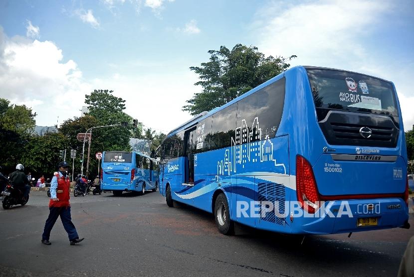 Petugas mengatur bus transjakarta koridor enam di lampu merah halte transjakarta Departemen Pertanian, Jakarta, Selasa (24/1).