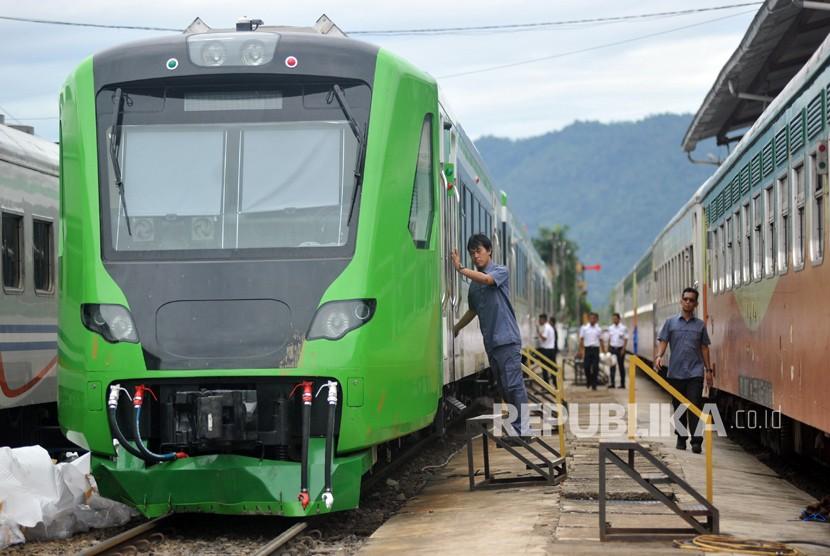 Petugas mengecek kondisi Kereta Rel Diesel Elektrik (KRDE) Bandara Internasional Minangkabau (BIM), seusai membuka pembungkus terpal, di Stasiun Simp Haru, Padang, Sumatera Barat, Jumat (23/2).